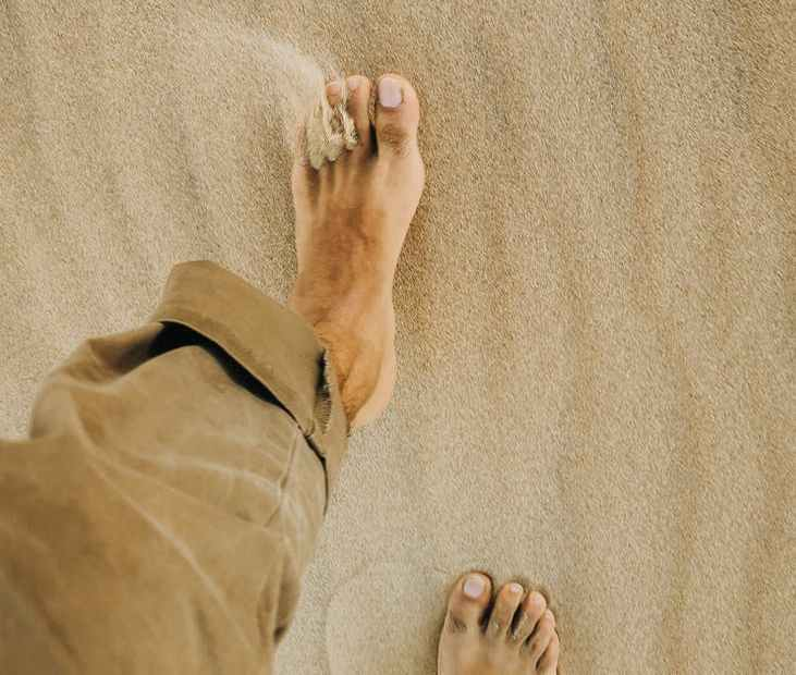 crop barefooted person walking on sandy beach