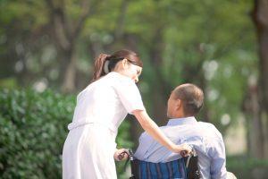 Nurse Pushing Man in Wheelchair