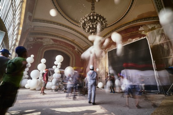 Long exposure of people pushing up the balloons to the big chandelier
