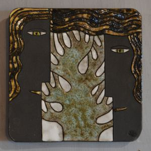 ceramic plaque with couple in front of bare tree