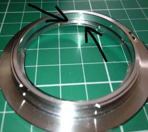 Gently widen the narrow slit between these parts to make the adapter a tight fit on the lens.