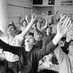 cult followers worshipping with arms raised