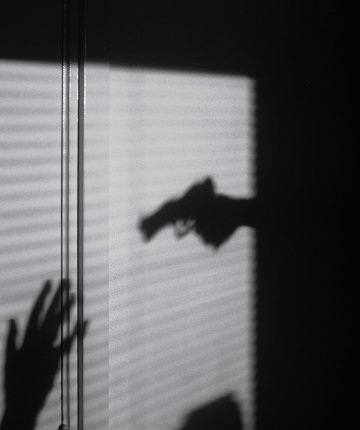 silhouette person pointing gun at someone