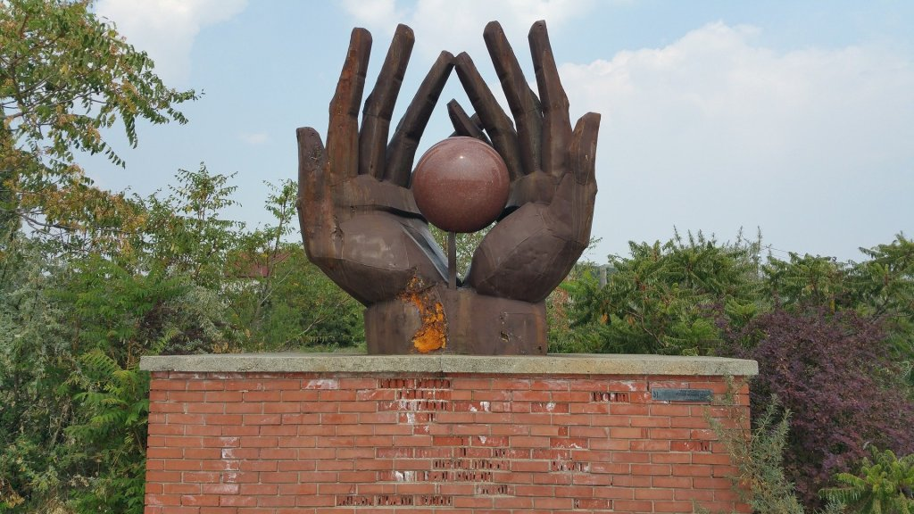 statue of two hands with ball