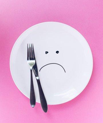 sad face drawn on empty plate