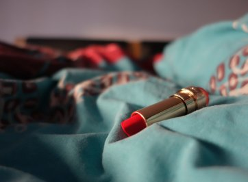 tube of red lipstick on sheet