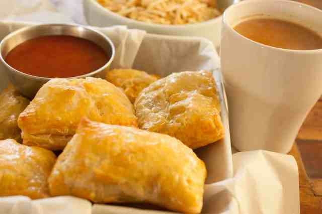 This is an image of indian chicken puffs with tea on the side, ketchup as dipping and some tapioca chips