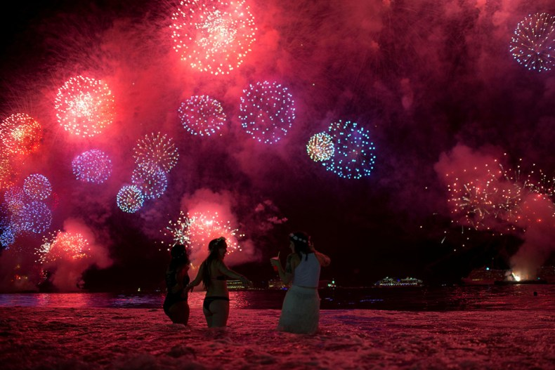 People watch as fireworks explode over Copacabana Beach during New Year's Eve celebrations in Rio de Janeiro, Brazil. [Lucas Landau/Reuters]