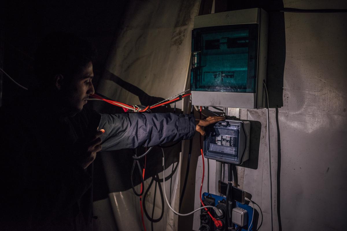 Ένας συριακός πρόσφυγας δείχνει τον κύριο διακόπτη ηλεκτρικής ενέργειας μέσα σε μια μεγαλύτερη σκηνή, που φιλοξενεί εκατοντάδες ανθρώπους.  «Δεν υπάρχει ηλεκτρικό ρεύμα εδώ και εβδομάδες και εδώ είναι συχνά πιο κρύο από το εξωτερικό», είπε.  [Kevin McElvaney / Al Jazeera]