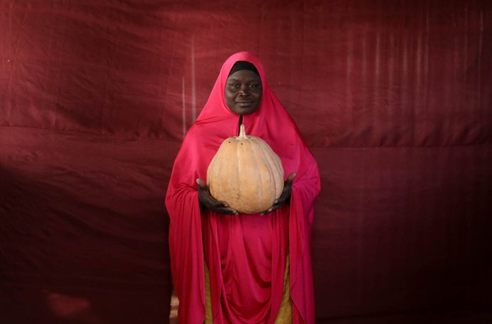 Aisha Umaru Gaye holds up a pumpkin. [Afolabi Sotunde/Reuters]