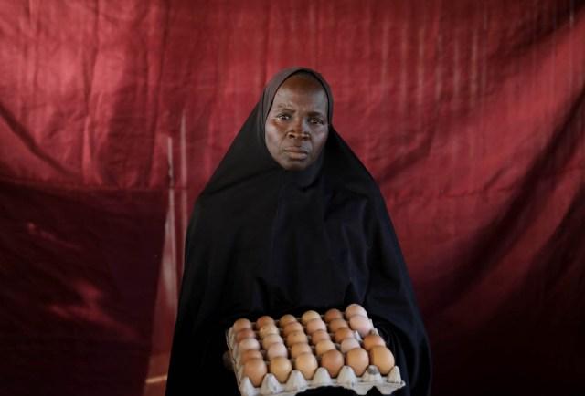 Famta Musa Tamaha holds a carton of eggs. [Afolabi Sotunde/Reuters]