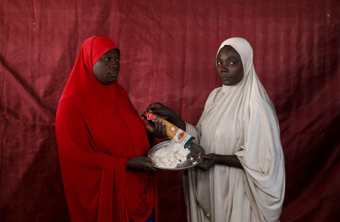 Zainab Umar gives parboiled soy bean paste to Aisha Jaule in exchange for spaghetti. [Afolabi Sotunde/Reuters]