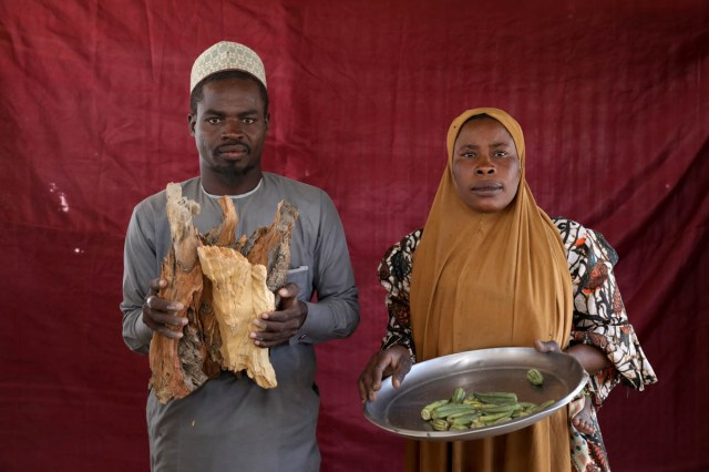 Isa Zakariya Audu (L) holds pieces of firewood while Kakaye Ahmadu Maikifi holds up a plate of okra. [Afolabi Sotunde/Reuters]