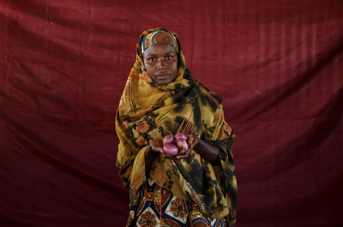 Aisha Alhajji Audu holds four small red onions in her hand. [Afolabi Sotunde/Reuters]