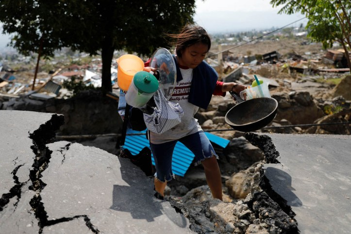 A girl carries valuables from the ruins of her house after the earthquake hit the Balaroa sub-district in Palu. [Beawiharta/Reuters]