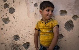 A child leans against the bullet-riddled wall of his house. Three years ago, ISIL took control of the neighbourhood and Kaiwan suffered burns to his left arm while fleeing with his family. The scars of conflict are still fresh on the child's body and the city's walls. [Tom Peyre-Costa/NRC]
