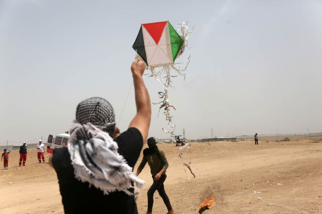 A Palestinian launches a kite carrying a Molotov cocktail over the border fence during the third week of the March. [Mohammed Zaanoun/Active Stills/Al Jazeera]