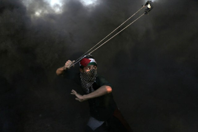 A Palestinian swings his slingshot in a cloud of thick smoke during the 26th Friday protest of the Great March of Return. Palestinians burn tyres to create a heavy smokescreen that obstructs the Israeli snipers' line of sight. [Mohammed Zaanoun/Active Stills/Al Jazeera]