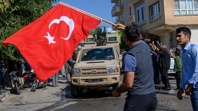 A man waves a Turkish flag as Turkey-backed Syrian opposition fighters going to Tel Abyad from Turkish gate towards Syria in Akcakale in Sanliurfa province on October 10, 2019. Turkey has launched a b