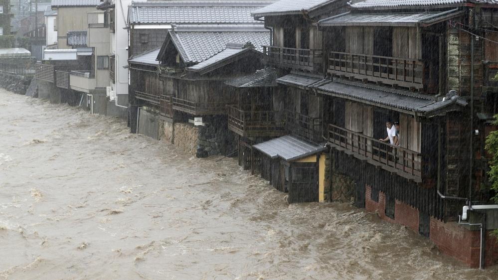 Men watch the swollen Isuzu River due to heavy rain caused by Typhoon Hagibis in Ise