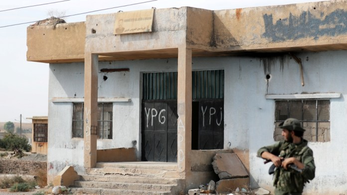 Turkey-backed Syrian rebel fighter stands near a former YPG office at the entrance of Tel Abyad, Syria, October 14, 2019