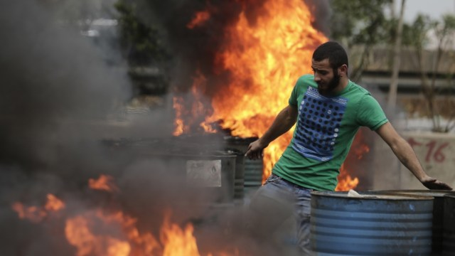 An anti-government protester sets fire to tires to block a highway that links the capital Beirut to northern Lebanon during a protest against the Lebanese government in Zouk Mosbeh, north of Beirut, L