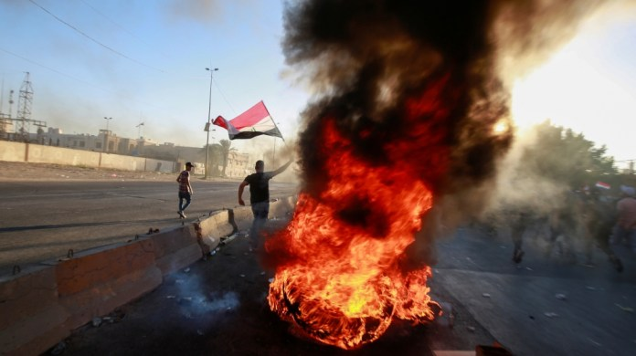 A demonstrator holds the Iraqi flag near burning objects at a protest during a curfew, three days after the nationwide anti-government protests turned violent, in Baghdad, Iraq October 4, 2019