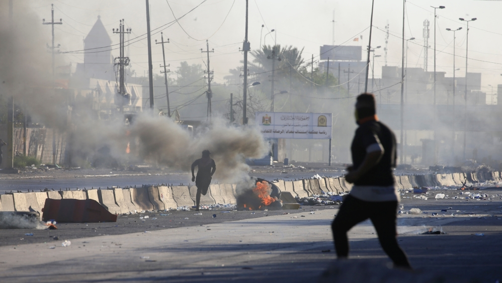 A man runs near burning objects at a protest during a curfew, three days after the nationwide anti-government protests turned violent, in Baghdad, Iraq October 4, 2019