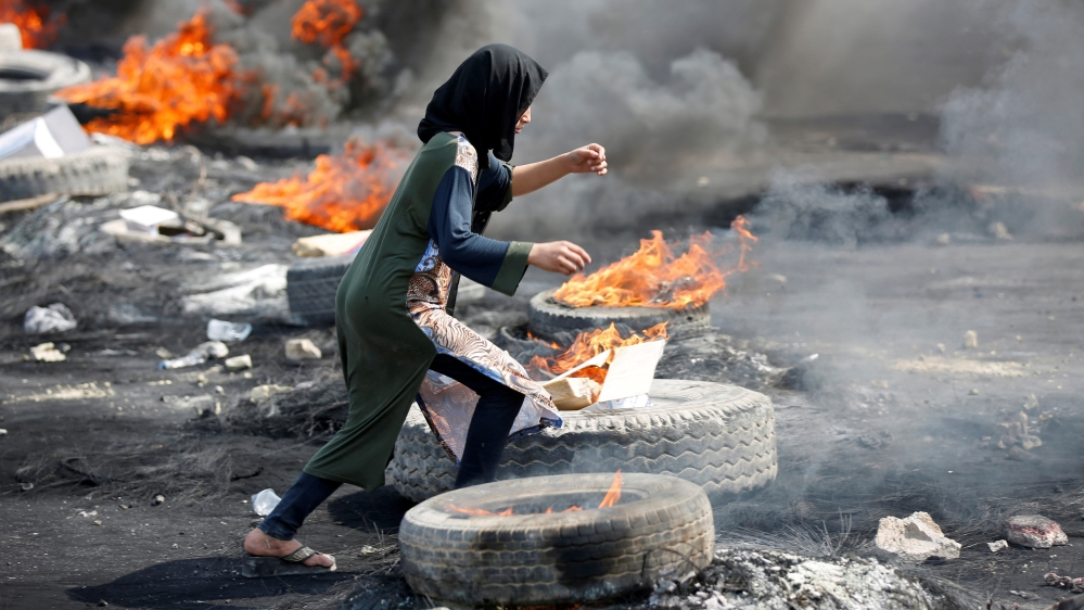 A demonstrator runs between burning tires during a curfew, two days after the nationwide anti-government protests turned violent, in Baghdad, Iraq October 3, 2019
