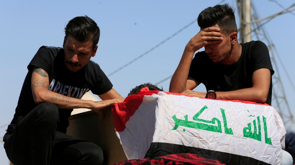Iraqi men mourn over the coffin of a demonstrator who was killed at anti-government protests, during a funeral in the holy city of Najaf, Iraq October 5, 2019