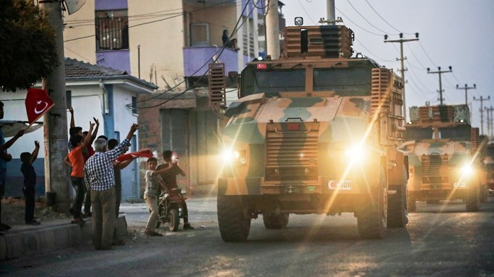 Shortly after the Turkish operation inside Syria had started, local residents cheer and applaud as a convoy of Turkish forces vehicles is driven through the town of Akcakale, Sanliurfa province, south
