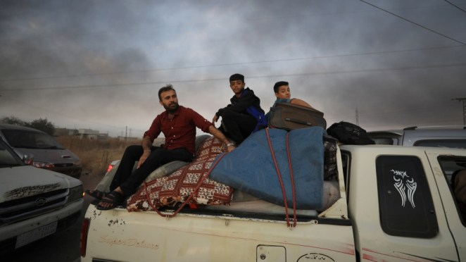 People sit on belongings at a back of a truck as they flee Ras al Ain town, Syria October 9, 2019
