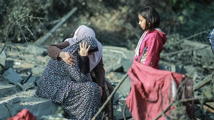 KHAN YUNIS, GAZA - NOVEMBER 13: Palestinian women sit on debris after Israeli airstrikes hit their homes in Khan Yunis, Gaza as tension rises between Israel and Gaza after commander in the Al-Quds Bri