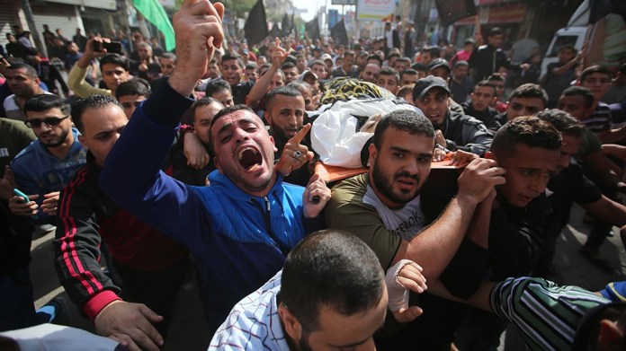 DEIR AL BALAH, GAZA - NOVEMBER 13: (EDITOR'S NOTE: Image depicts death) People carry the dead body of a 38-year-old Khalid Muavvad Ferrac, who was killed in Israeli airstrikes over Deir al Balah, duri