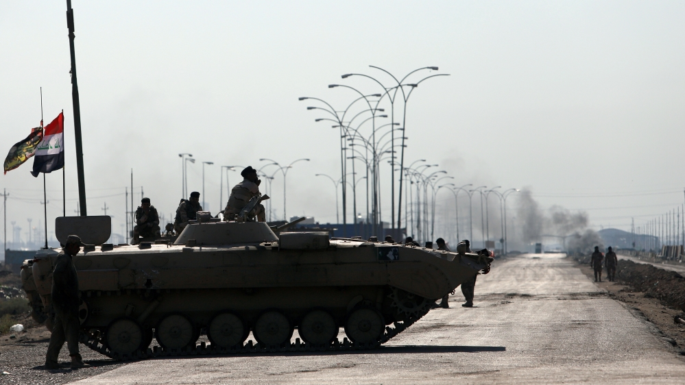 Iraqi army forces guards at the entrance of Umm Qasr Port as protesters block the road during ongoing anti-government protests, south of Basra
