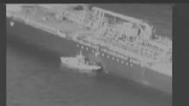 Still image taken from a U.S. military handout video purports to show Iran's Revolutionary Guard (IRGC) removing an unexploded limpet mine from the side of the Kokuka Courageous Tanker