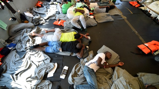 Migrants lie on board the rescue ship Sea-Watch 3 as it remains blocked one mile outside the port of Lampedusa