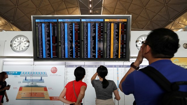 Passengers react as they check the flight information board as the airport reopened a day after flights were halted due to a protest, at Hong Kong International Airport, China August 13, 2019. REUTERS