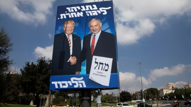 A man walks past a Likud party election campaign banner depicting Israeli Prime Minister Benjamin Netanyahu and U.S. President Donald Trump as a labourer hangs it up in Jerusalem