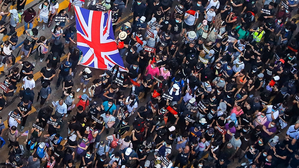 Protesters carry a British flag gather at a shopping district during a rally in Hong Kong, Sunday, Sept. 15, 2019. Thousands of Hong Kong people chanted slogans and marched Sunday at a downtown shoppi