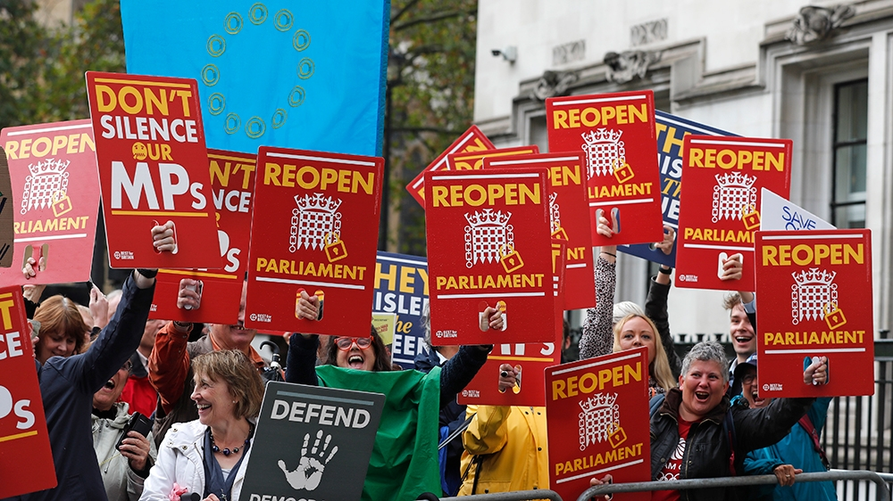 Anti-Brexit supporters react as they gather outside the Supreme Court in London, Tuesday, Sept. 24, 2019 as it makes it's decision on the legality of Prime Minister Boris Johnson's five-week suspensio