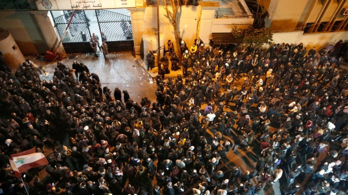 Anti-government protesters gather outside a police headquarters, as they demand the release of those taken into custody the night before, outside a police headquarter, in Beirut, Lebanon, Wednesday