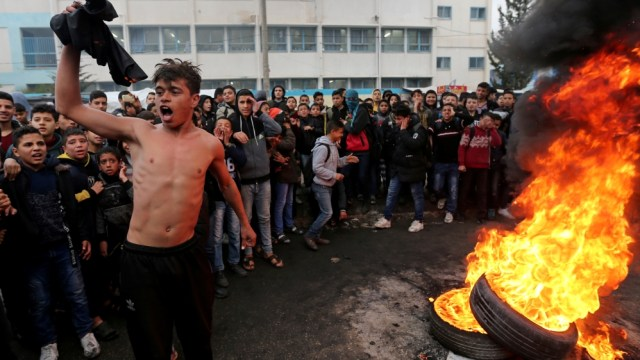Palestinian students protest against the U.S. President Donald Trump's Middle East peace plan as tires burn, in the southern Gaza Strip