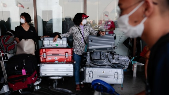 Passengers wearing masks stand by with their luggage outside the Ninoy Aquino International Airport in Paranaque, Metro Manila