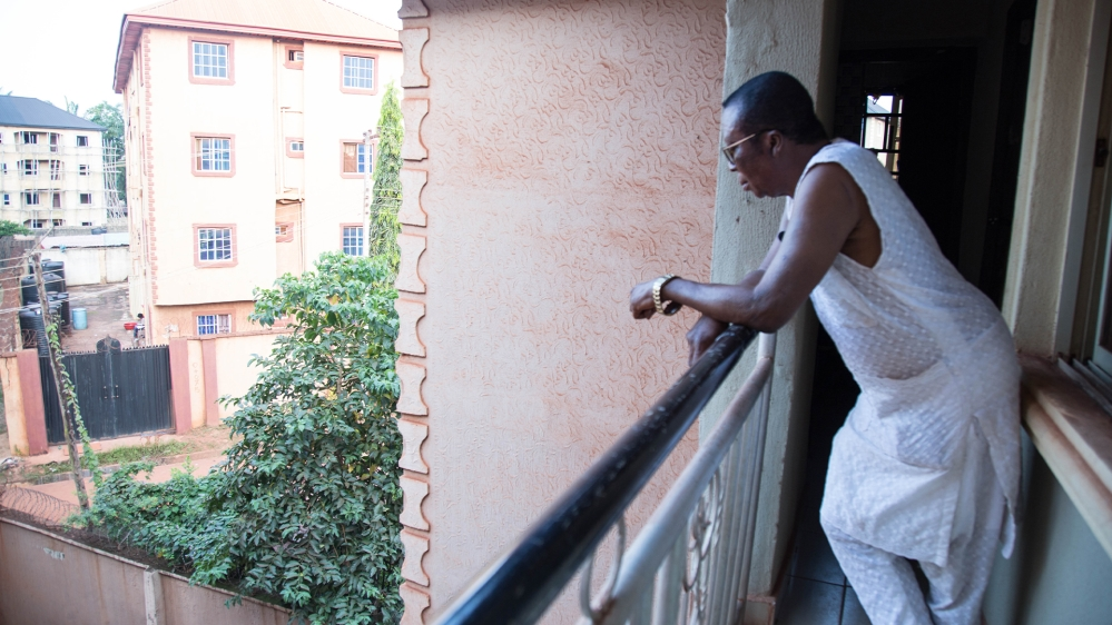 Kanu at the balcony of his apartment looking outside the neighbourhood