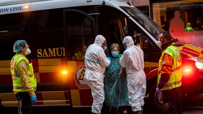 A patient, center, is transferred to a medicalised hotel during the COVID-19 outbreak in Madrid, Spain, Tuesday, March 24, 2020. For most people, the new coronavirus causes only mild or moderate sympt