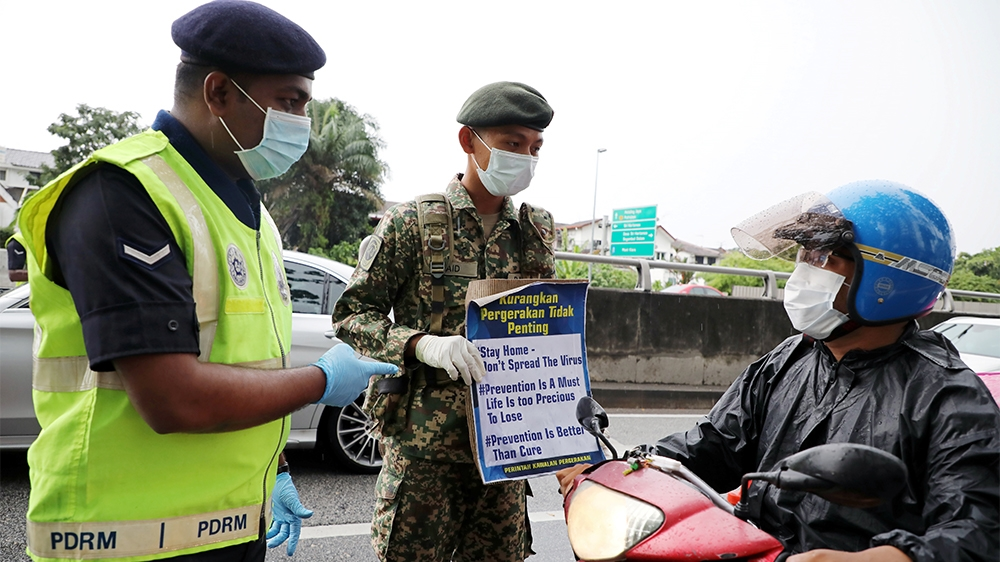 A soldier and a police officer wearing protective masks show a placard to a motorcyclist at a roadblock set up to enforce movement control order due to the outbreak of the coronavirus disease (COVID-1