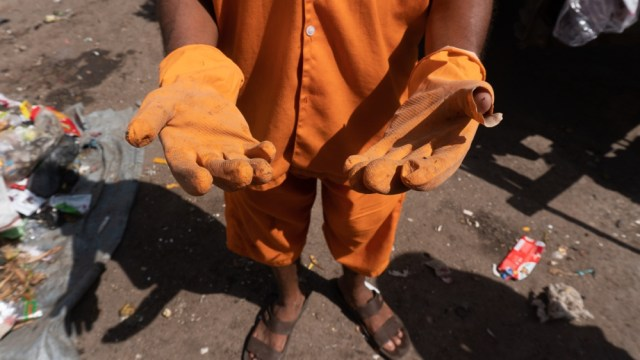 A contract worker shows the pair of gloves he received from the government, that became torn in a day [Shone Satheesh Babu/Al Jazeera]