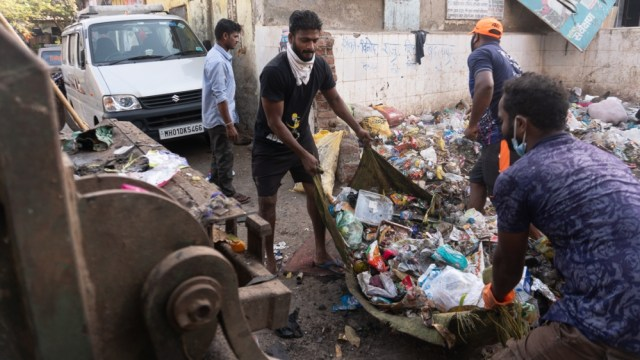 Workers sort through the garbage to remove pieces of glass or concrete which is not allowed to be put in the garbage truck [Shone Satheesh Babu/Al Jazeera]