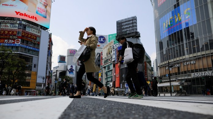Less than usual pedestrians cross the Shibuya crossing after the government announced the state of emergency for the capital following the coronavirus disease outbreak in Tokyo, Japan